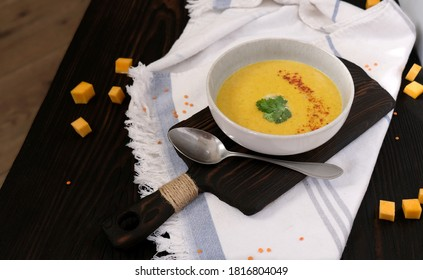 Cream soup with pumpkin and red lentils with spices in the grey bowl on the dark wood board. Rustic background