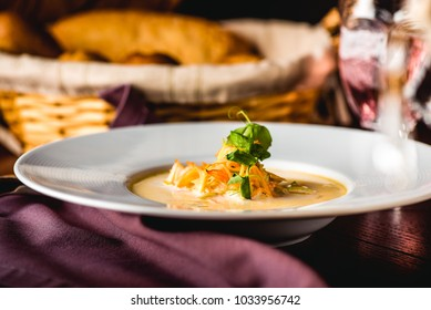Cream soup with shrimps and carrots in big dish. Bread in basket, lemonade in glass. Wooden table, textile napkin. Close up