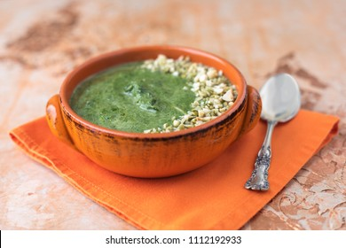 Cream of Spinach Soup in an Orange Bowl with Peanuts and Pumpkin Seeds Topping