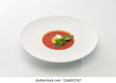 cream of tomato soup with cheese and basil in a plate isolated on white background.