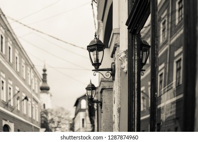 Cream tone, monochromatic. Alley in the old town of Cluj Napoca, Romania. Narrow cobbled street in old medieval town with illuminated houses by vintage street lamps.