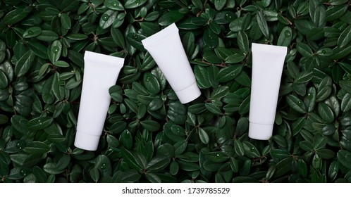 Cream tube mock up, set of three white cream tubes on a background of green leaves, organic cosmetics mockup, packaging design