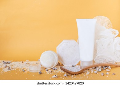 cream in a white tube, soap, washcloth, sea salt in a spoon, shells on yellow background. copy space