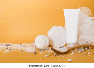 cream in a white tube, soap,washcloth, sea salt in a spoon, shells on yellow background. copy space