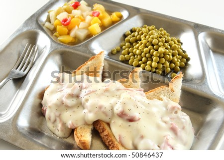 Creamed Chipped Beef on Toast on a metal tray with canned peas and fruit salad
