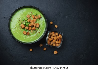 Cream-soup with green peas and rusks, flatlay on a black stone background with copyspace, horizontal shot