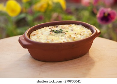 Creamy baked macaroni and cheese in a clay pot