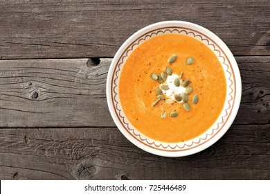 Creamy butternut squash soup, above view on a rustic wood background