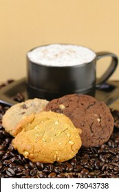 A creamy cappuccino in a black cup with three cookies on a bed of coffee beans with a shallow DOF.