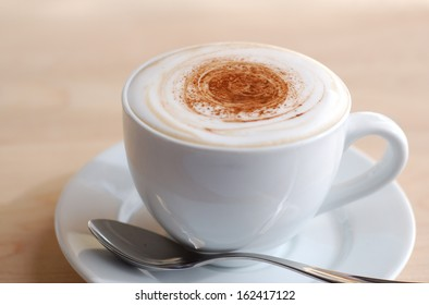 Creamy cappuccino on wooden surface with copy space.