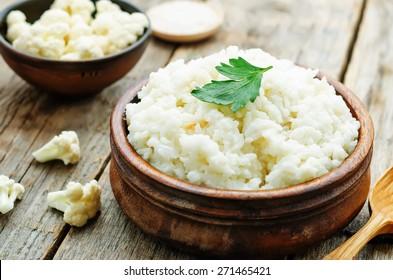 creamy cauliflower garlic rice on a dark wood background. the toning. selective focus