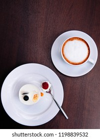 Creamy cheesecake with with raspberry blueberry on white dish and cappucino coffee cup on wood table in bekery cafe. Top view food shot