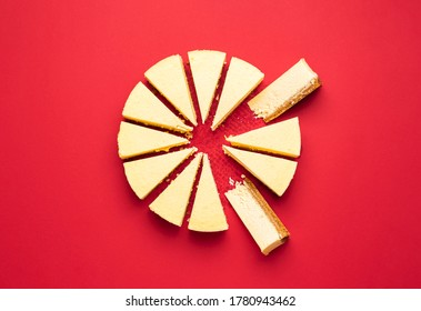 Creamy cheesecake sliced with interior section, isolated on a red background. Top view of delicious cheese pie slices. Sliced cake. Christmas dessert.