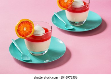 Creamy Citrus Fruit Panna Cotta with Blood Orange Jelly and Whipped Cream on Minimalist Solid Pink Background