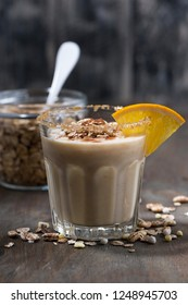 creamy cocktail with oats on dark background, vertical closeup