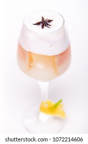 creamy cocktail with orange at wineglass on white background