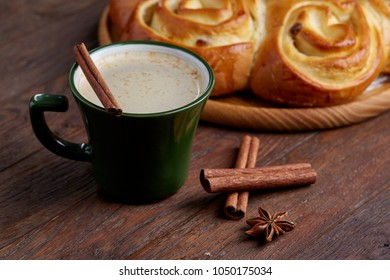 Creamy coffee in cup with homemade rose bread on vintage wooden background, close-up, selective focus