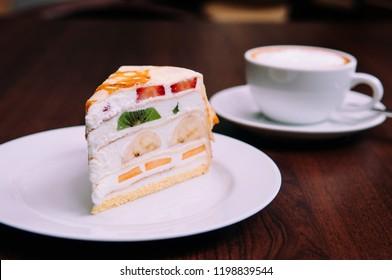 Creamy Crepe cake with mix fruits, strawberry, Kiwi, banana on white dish in bekery cafe
