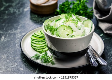 Creamy cucumber dill salad with yogurt dressing on dark marble background. Selective focus, space for text.
