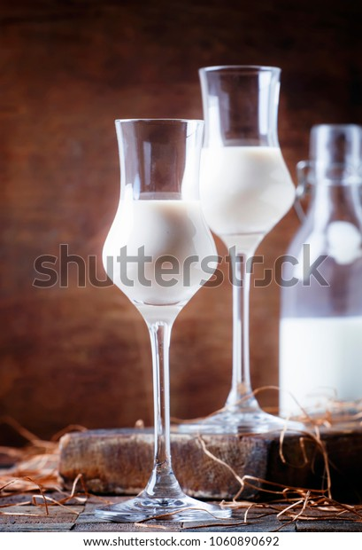Creamy liqueur in shot glasses, rustic style, vintage wooden background, selective focus