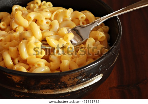 Creamy macaroni and cheese in stoneware bowl on wood background.  Macro with shallow dof.  Focus on fork.