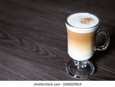 A creamy Macchiato or cappucino coffee in a tall glass with a clean background