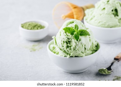 Creamy Matcha Green Tea Ice Cream with mint leaves in white bowl copy space