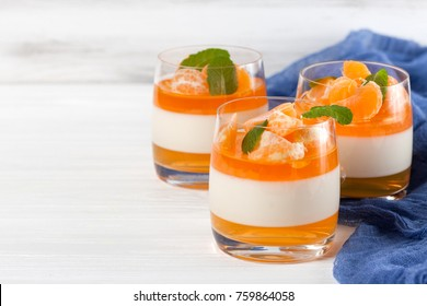 Creamy panna cotta with orange jelly in beautiful glasses and fresh ripe mandarin with blue textile on white wooden background. Closeup photography of delicious dessert.