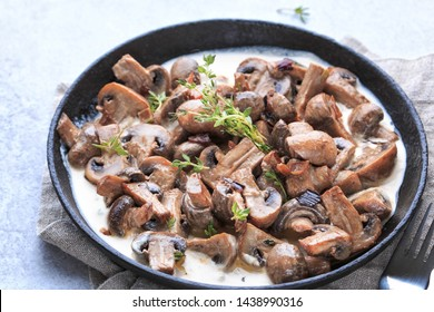 Creamy Parmesan Garlic Mushroom in pan, on wooden background. Creamy mushroom vegetarian recipe.