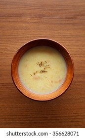 creamy potato soup in wooden bowl