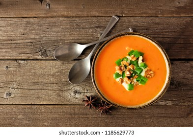 Creamy pumpkin soup. Autumn food concept. Top view on a rustic wood background.