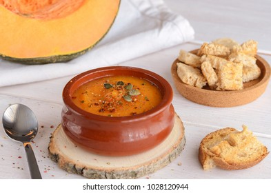 Creamy pumpkin soup with pumpkin seeds and spice, served in ceramic bowl and fresh toasts on wooden table. Easy healthy plate for dinner. Vegetarian diet and lifestyle.