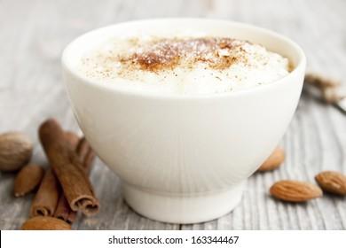 creamy rice pudding with cinnamon powder,cinnamon sticks and almonds