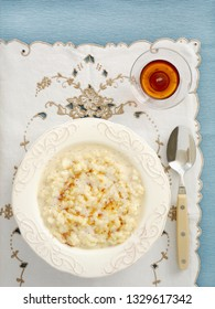 Creamy rice pudding with maple syrup in decorated bowl on embroidered placeman from overhead.
