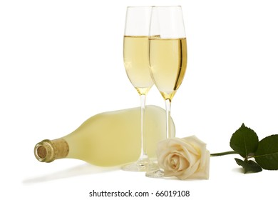creamy rose in front of two champagne glasses and a dull prosecco bottle on white background