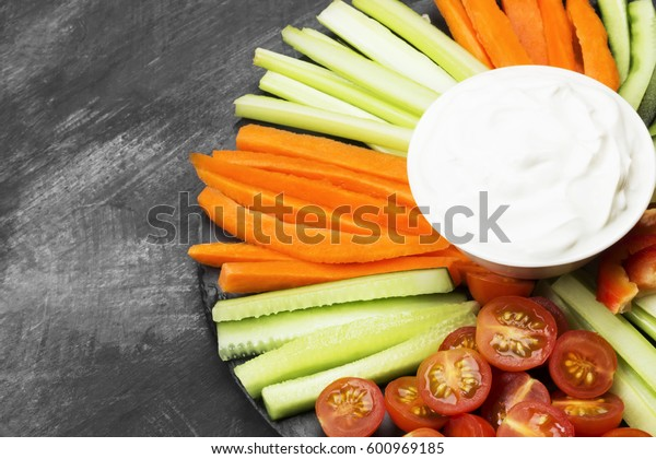 Creamy sauce in white bowl and various vegetables (tomatoes, a celery, cucumbers, carrots) on a dark background. Copy space. Food background.