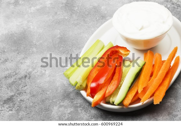 Creamy sauce in white bowl and various vegetables (pepper, celery, cucumbers, carrots). Copy space. Food background