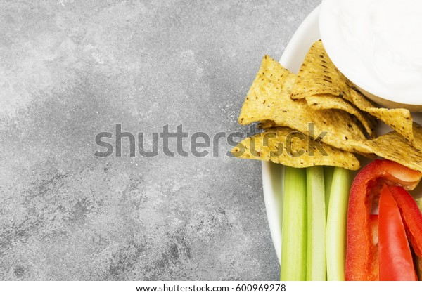 Creamy sauce in white bowl, various vegetables (celery, pepper) and nachos. Top view, copy space. Food background.