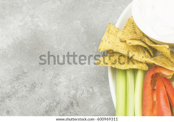 Creamy sauce in white bowl, various vegetables (celery, pepper) and nachos. Top view, copy space. Food background. Toning