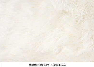 Creamy shaggy blanket texture as background. Fluffy fake textile fur.