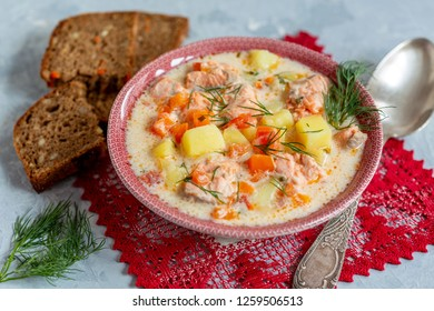 Creamy soup with salmon in bowl and slices of rye bread on a gray textured background, selective focus.