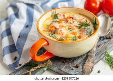 Creamy soup with salmon, potatoes, onions, carrots and green dill in a bowl on the serving board, selective focus.