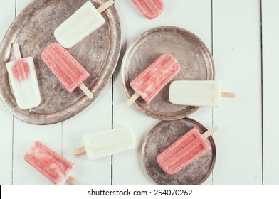 Creamy and strawberry popsicles and vintage dishes on a white wooden board, homemade food, summer dessert, filtered
