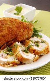 A creamy stuffed fried chicken with vegetable garnishing