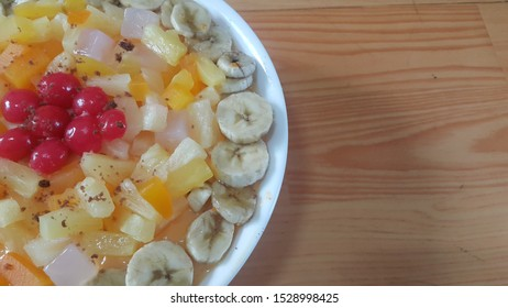 Creamy tasty sweet fruit trifle over custard with banana slices layered on surface on wooden floor. A top view of home made fruit trifle, a products for dessert after meal.