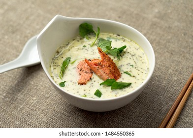 Creamy tom kha thai soup with salmon. One of the most popular Thai food, tom kha is a spicy and sour soup with coconut milk. Vermicelli noodles and salmon are added in this version of the dish.