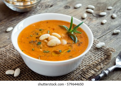 Creamy white bean and vegetable soup with rosemary on wooden background - healthy homemade diet vegetarian vegan soup meal food