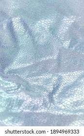 Creased textile texture, background template. Shine fabric light blue drapery. Sheene sharkskin fabrics for fashion dress. Shiny fashion clothing material sample.