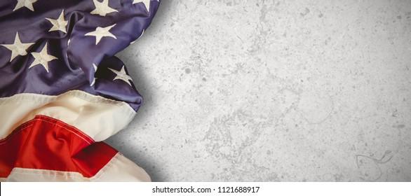 Creased US flag against grey background