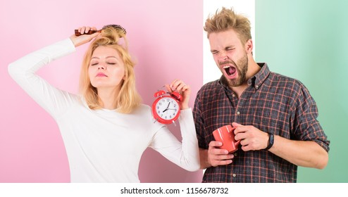 Create healthy rest regime to sleep enough. Regret late regime. We should go to bed earlier. Woman and man sleepy tousled hair drink morning coffee. Couple morning awakening alarm clock.